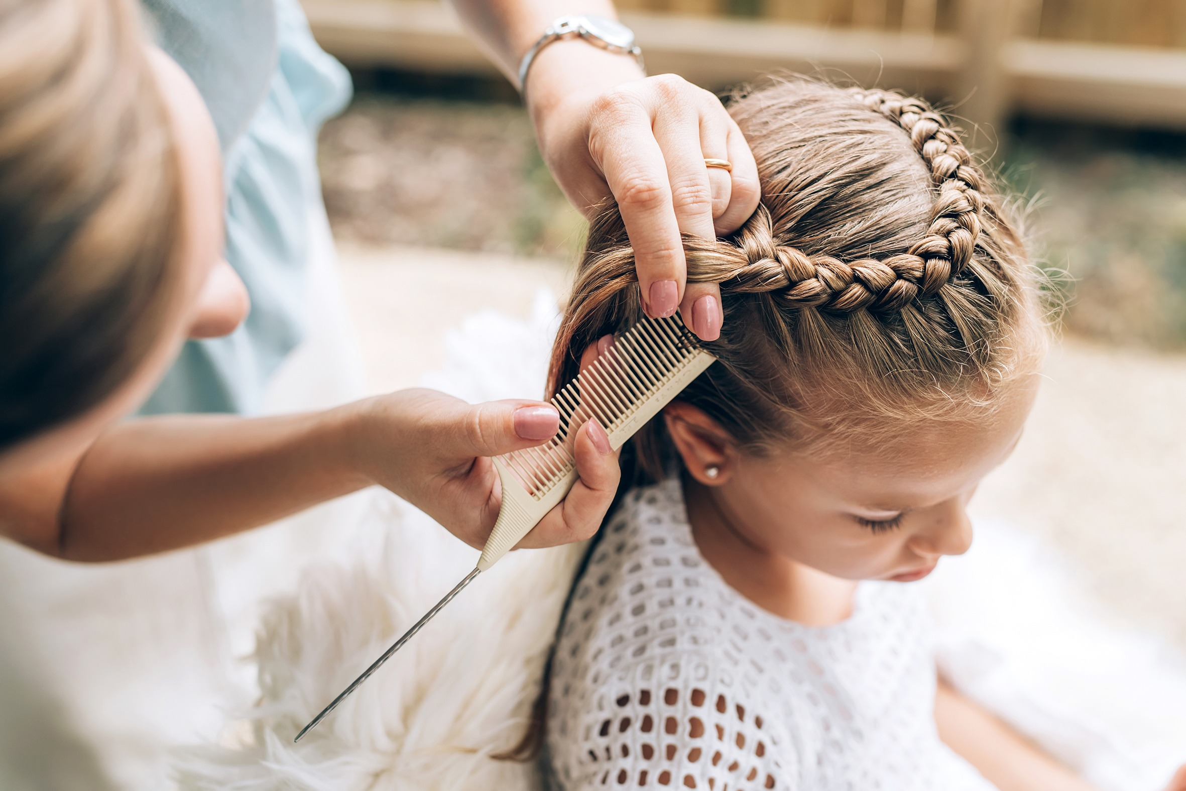 Mother does hair braid to her daughter, close up photo.