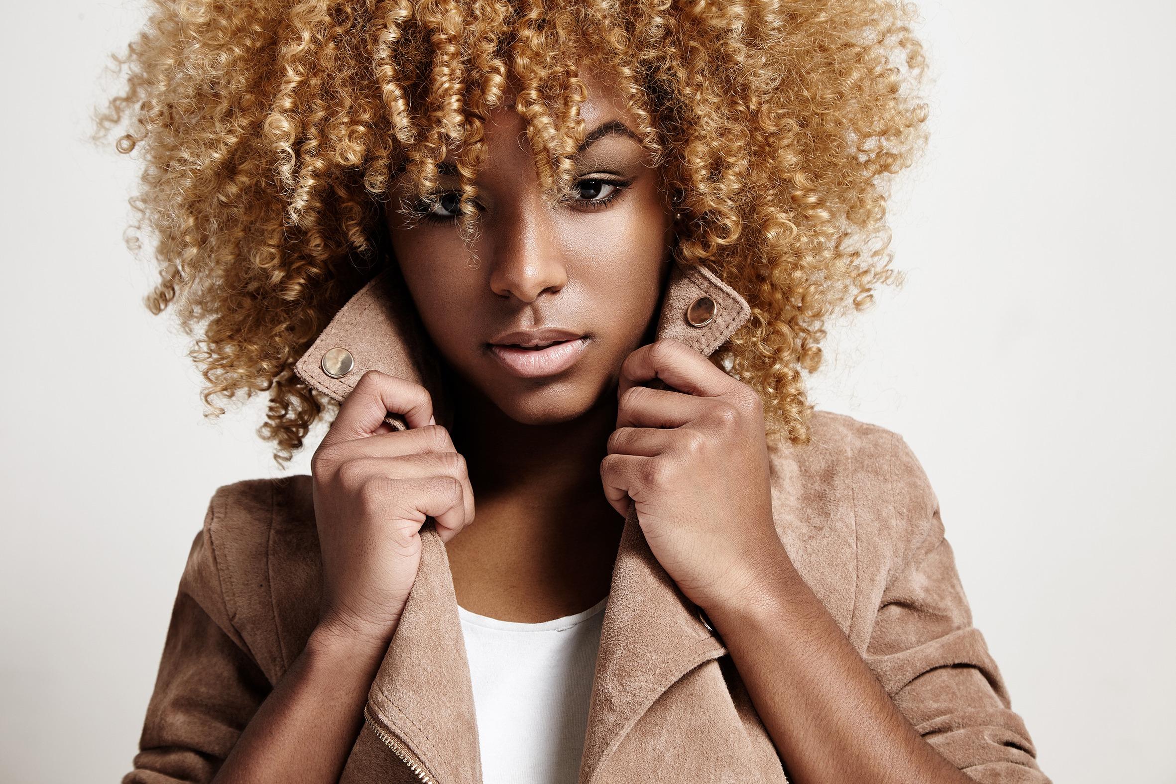 black woman wears beige jacket, curly hair
