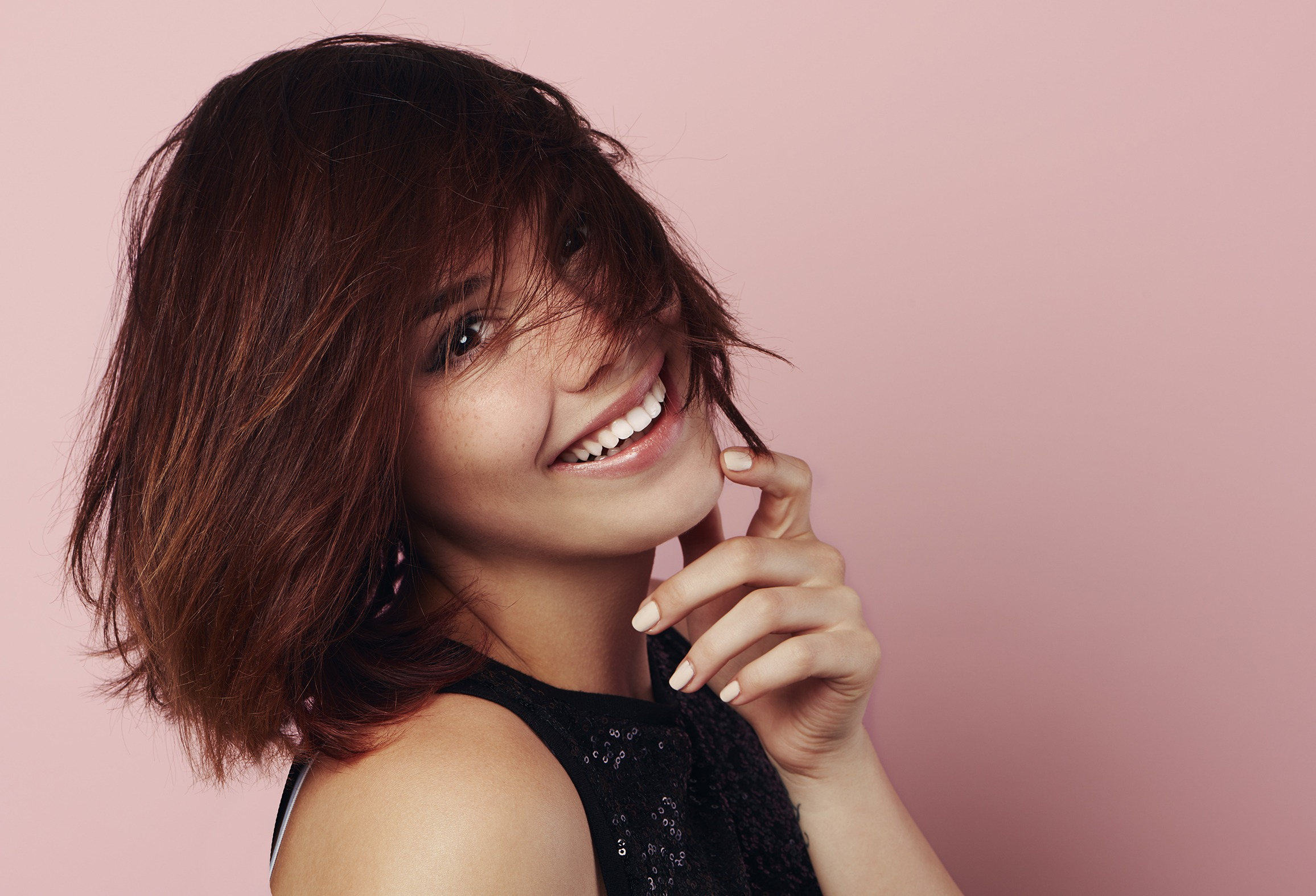 Beauty portrait of smiling female model with windy hair over pin